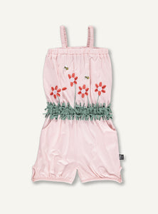 UBANG Pink Playsuit with an elasticated waist. It is embroided with flowers and has green grass at the waist made of fabric strips.