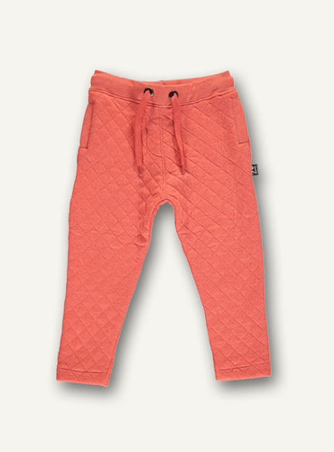 UBANG quilted pants in warm orange. They have drawstring at the waist.