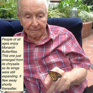 Older man with a Monarch Butterfly on his finger.