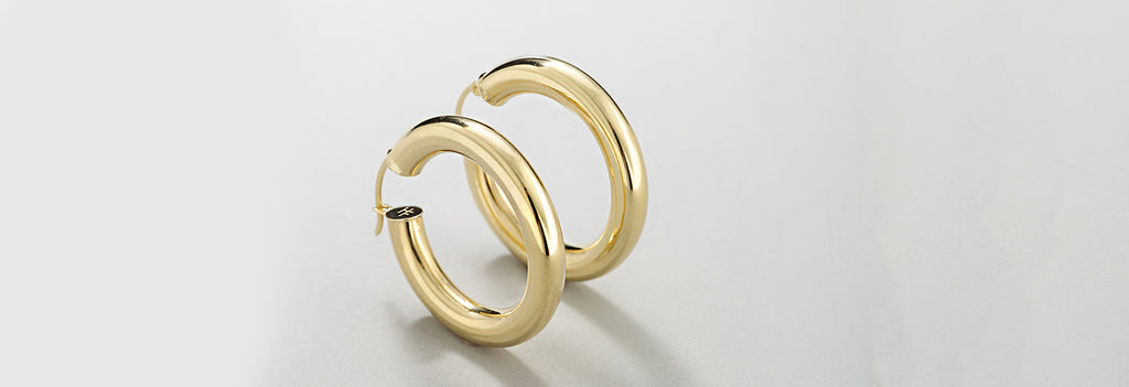 Our favorite new addition to our earrings collection are these big, beautiful golden chunky hoop earrings. Made with solid 14k yellow gold, these are one of a kind pair of hoops that will bling up any outfit.  Wear these beautiful hoops earrings with our 14k gold chains and charms too!
