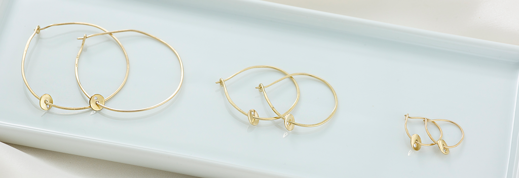They come in 14k yellow gold, white gold and rose gold, as well as in three sizes ranging from big and bold to small and dainty, all to match your personality and aesthetic. Wear these beautiful hoop earrings with our 14k gold chains and charms too!