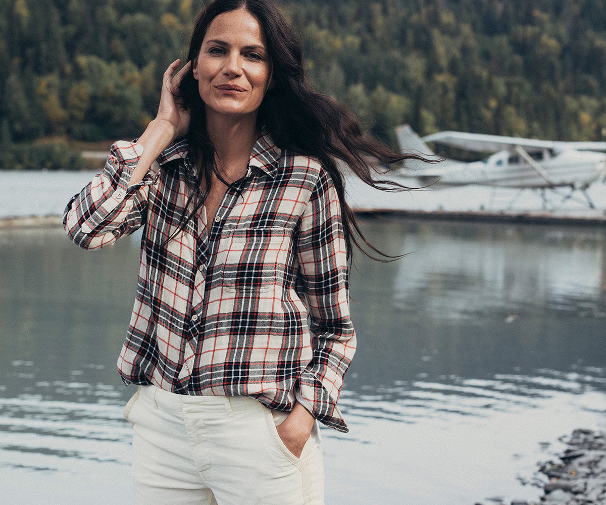 A woman in a flannel poses by a seaplane