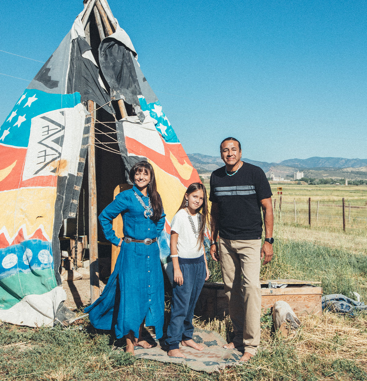 A Native American family stands in together in front of a teepee.