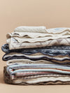 A slack of Faherty blankets in a studio setting.