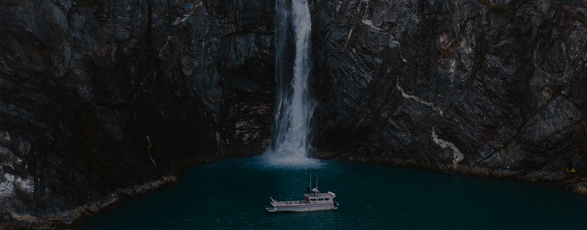 A boat idles at the base of a glacial waterfall.