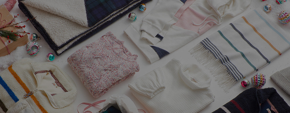 Several women's products from a jacket to pants laid out as gifts.