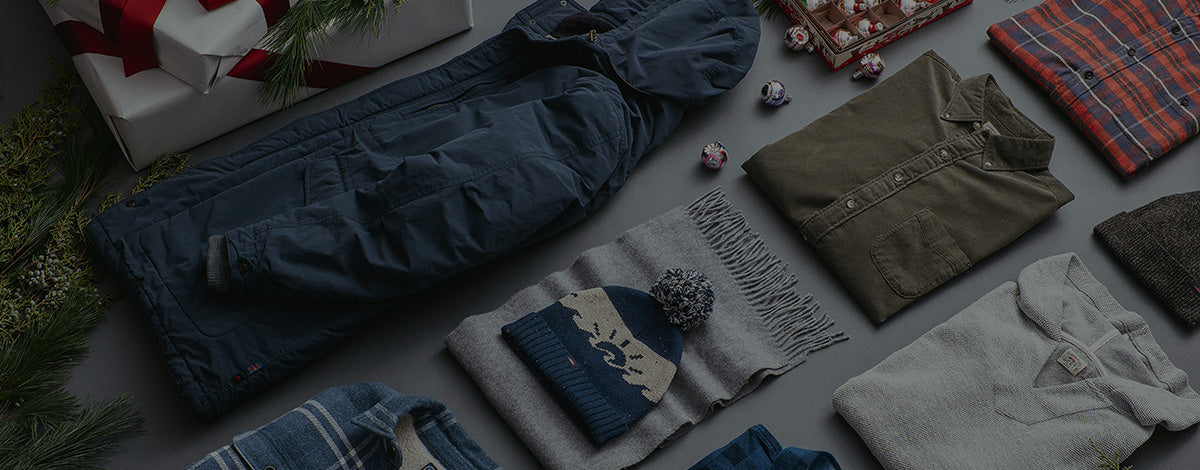 Several men's products from a jacket to pants laid out as gifts.