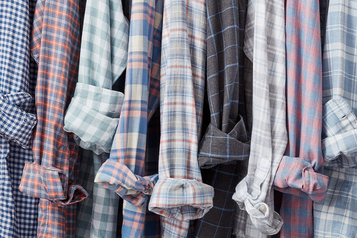 Long-sleeve button-up shirts hanging together with their sleeves rolled up.