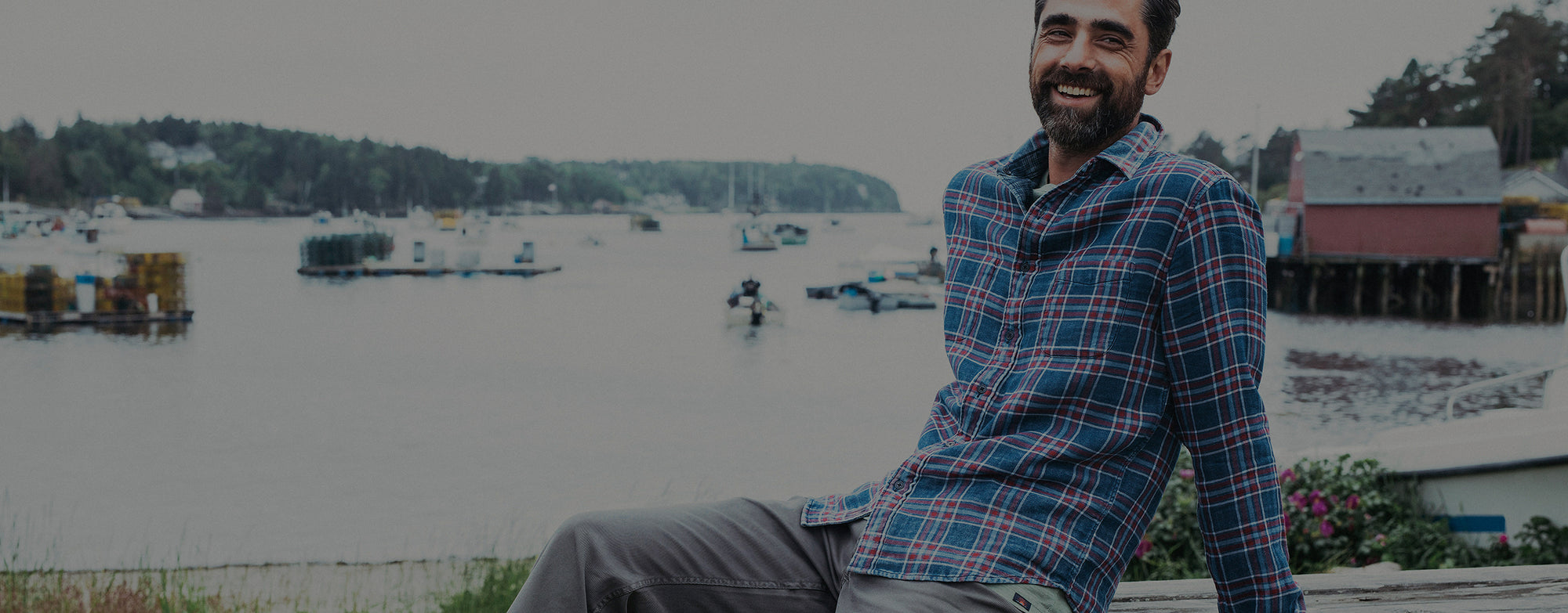 Man smiling in a reversible plaid shirt on the coast.