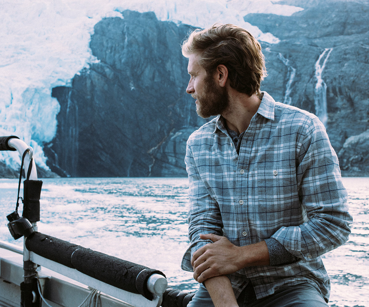A man in a flannel sits on a boat that's facing a glacier.