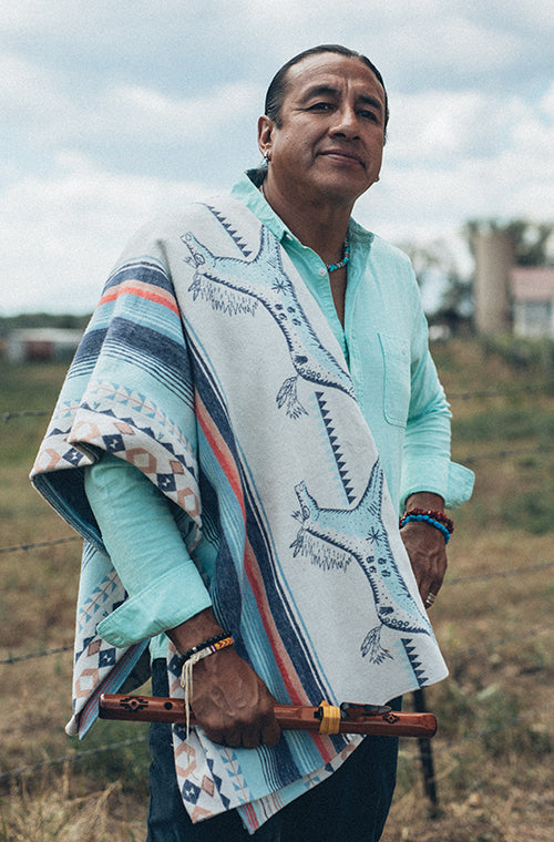 A man stands on a farm with a blanket over his shoulder.