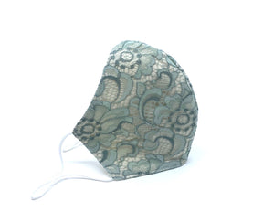 Scalloped Raschel lace mask in sage - a versatile green color defined by its grayish, silvery undertones. Lined with 2 layers of organic cotton twill.   Mask comes with optional adhesive nose wire and adjustable ear loops.