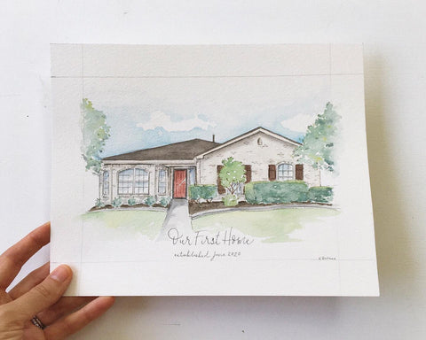 Hand holding a watercolor painting of a white house with red front door