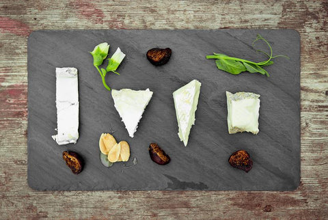 slate cheeseboard with olives on top