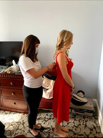 Founder, Heather, helps tie the back of a model wearing the Rachel dress