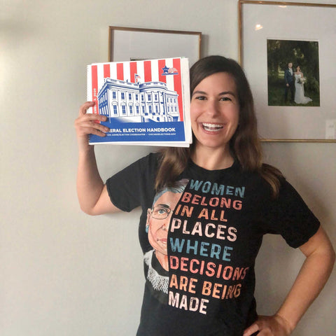 Heather, holding election day handbook in RBG shirt