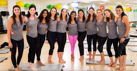 a group of women in a fitness studio, smiling and wearing Passion Fit branded workout gear
