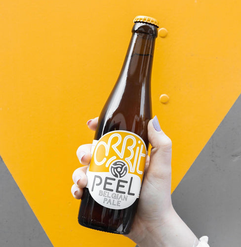 Peel Belgian Pale held up in a bottle