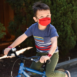 Boy Riding Bike with Mask from The Universal Mask