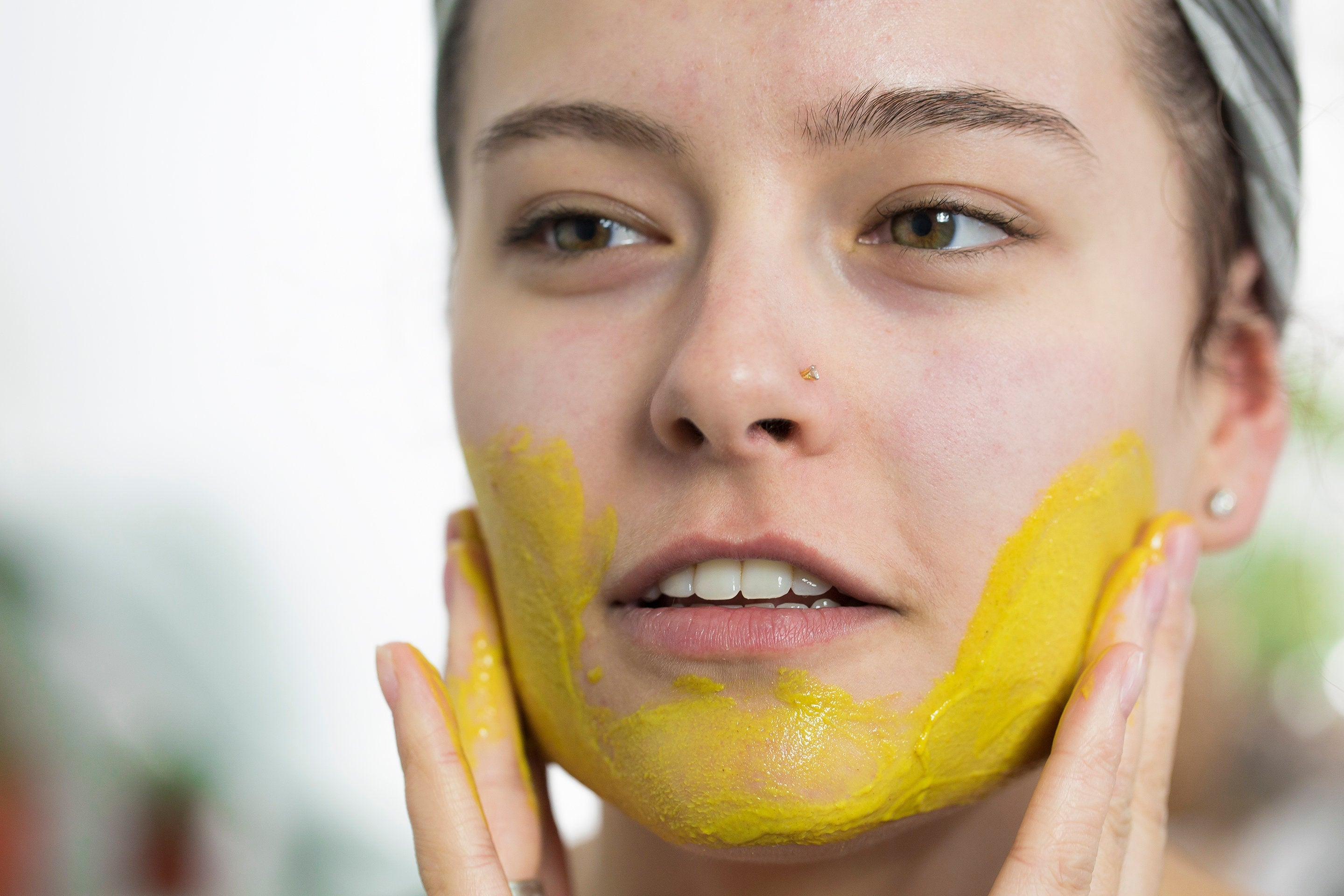 Woman applying SCHMEAR Naturals Superfood Skincare