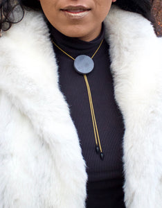 Concrete bolo tie necklace close up on a model
