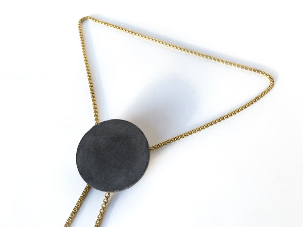 Side view of concrete pendant of bolo tie necklace