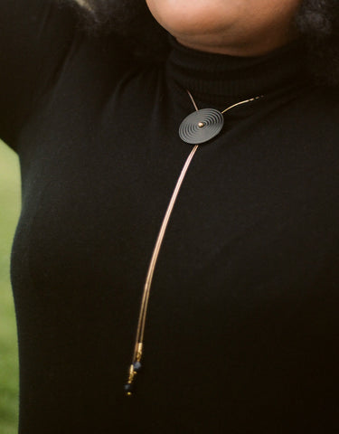 Close up of black bolo tie necklace