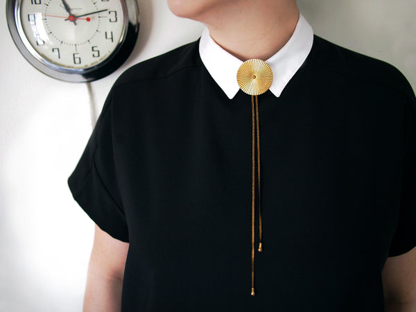 Model wearing gold and black bolo tie necklace