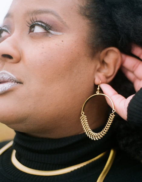 Brass fishbone chain earrings on a model