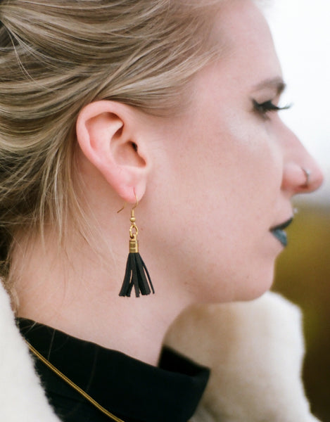 Side view of leather tassel earrings on model