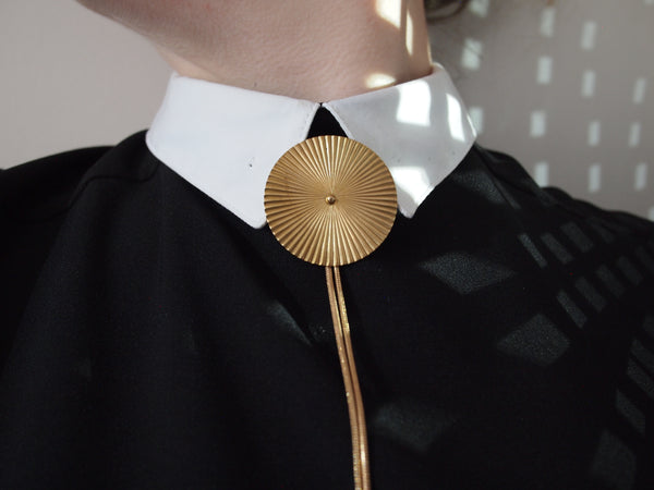 Bolo tie medallion on a collared shirt