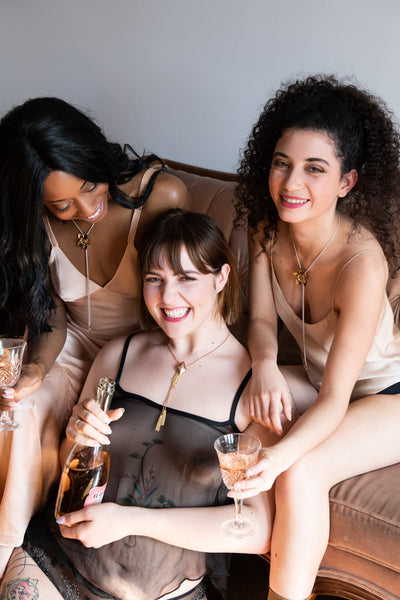 Models wearing flower bolo ti necklace and drinking champagne