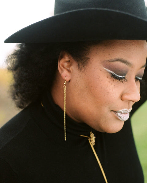 Side view of model wearing gold tassel earrings