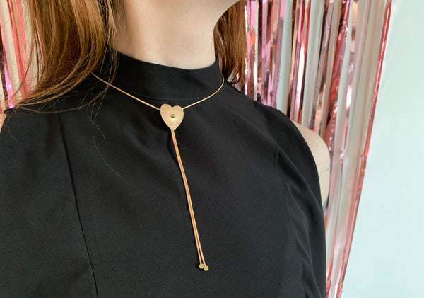 Close up of model wearing gold bolo tie