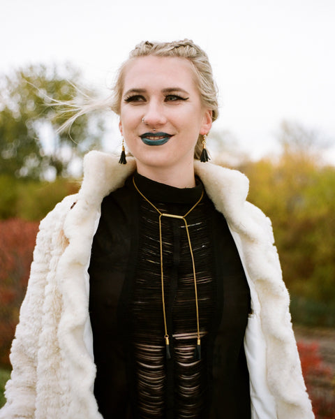 Model wearing recycled leather jewelry set