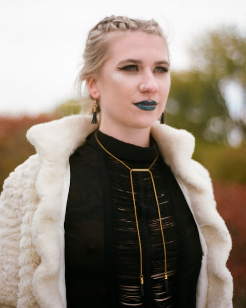 Model wearing matching matching leather tassel necklace and earrings