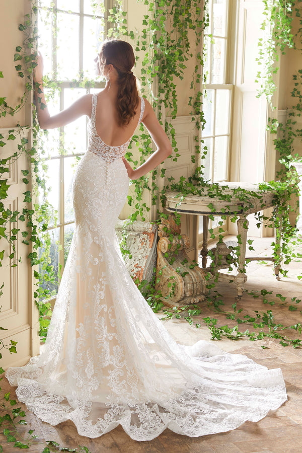 5711 by Mori Lee is a stunning ivory/champagne fit and flare all over lace gown with long sheer train and illusion neckline and plunging low scooped back. Stunning designer discounted dress amazing quality for cheap sale price.