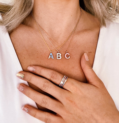 girl with a, b, c necklaces and rings on