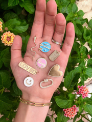 necklace charms in a hand