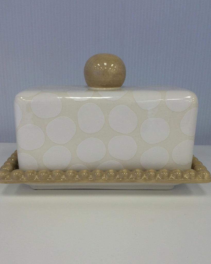 Light Taupe Butter Dish with white polka dots, large taupe knob to lift lid with and base is taupe with little pebbles all around it.