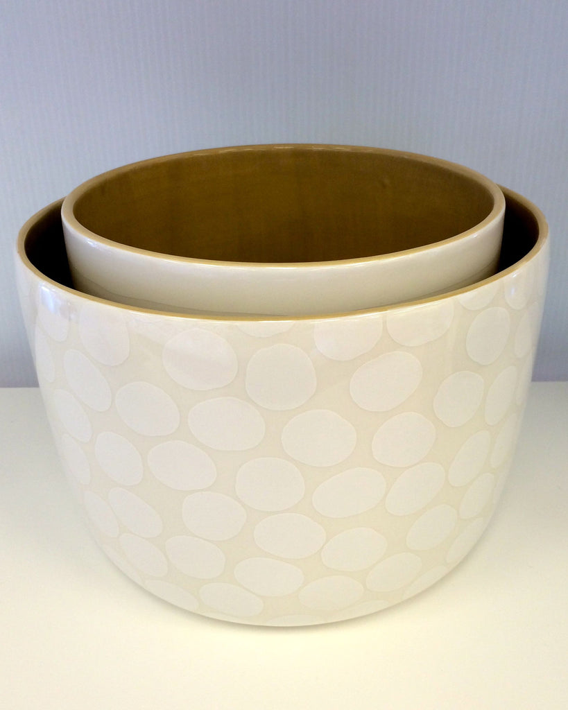 Large bowl has white polka dots on taupe background, Small bowl has white stripes running around the taupe colored bowl
