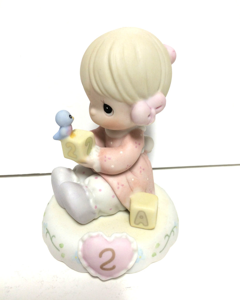 Blonde haired girl with pink dress holding abc building blocks with a blue bird sitting on top. Has 2 inside a pink heart on base.