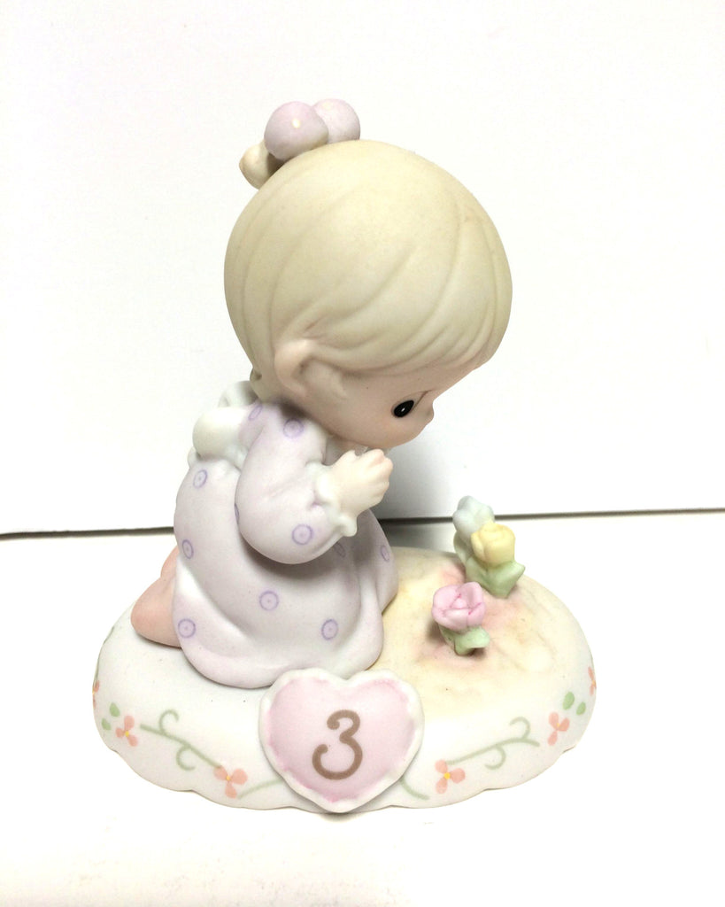 Blonde headed girl in lilac dress planting flowers. 3 on pink heart on base.
