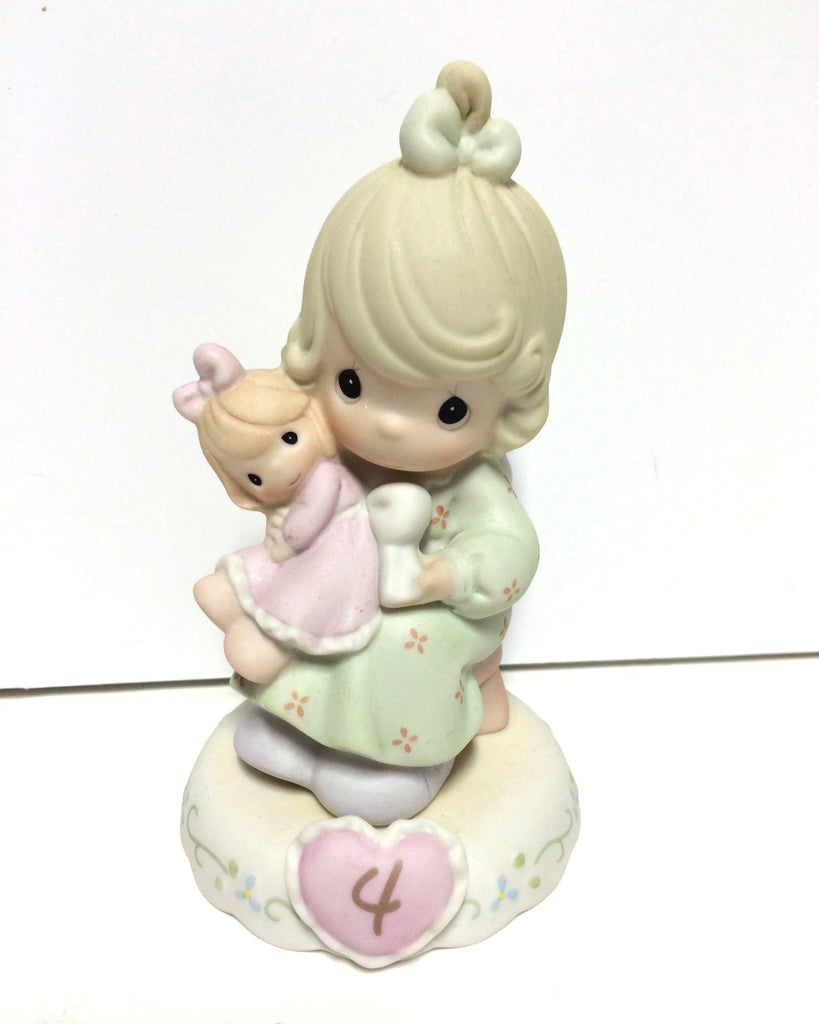 Blonde haired girl in green dress holding doll in pink. Has 4 inside of heart on base.