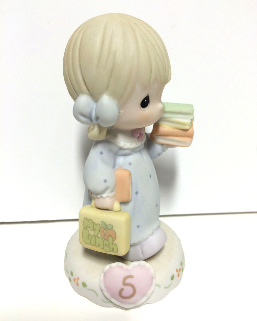 Blonde haired girl with books and lunch box. 5 inside pink heart on base.