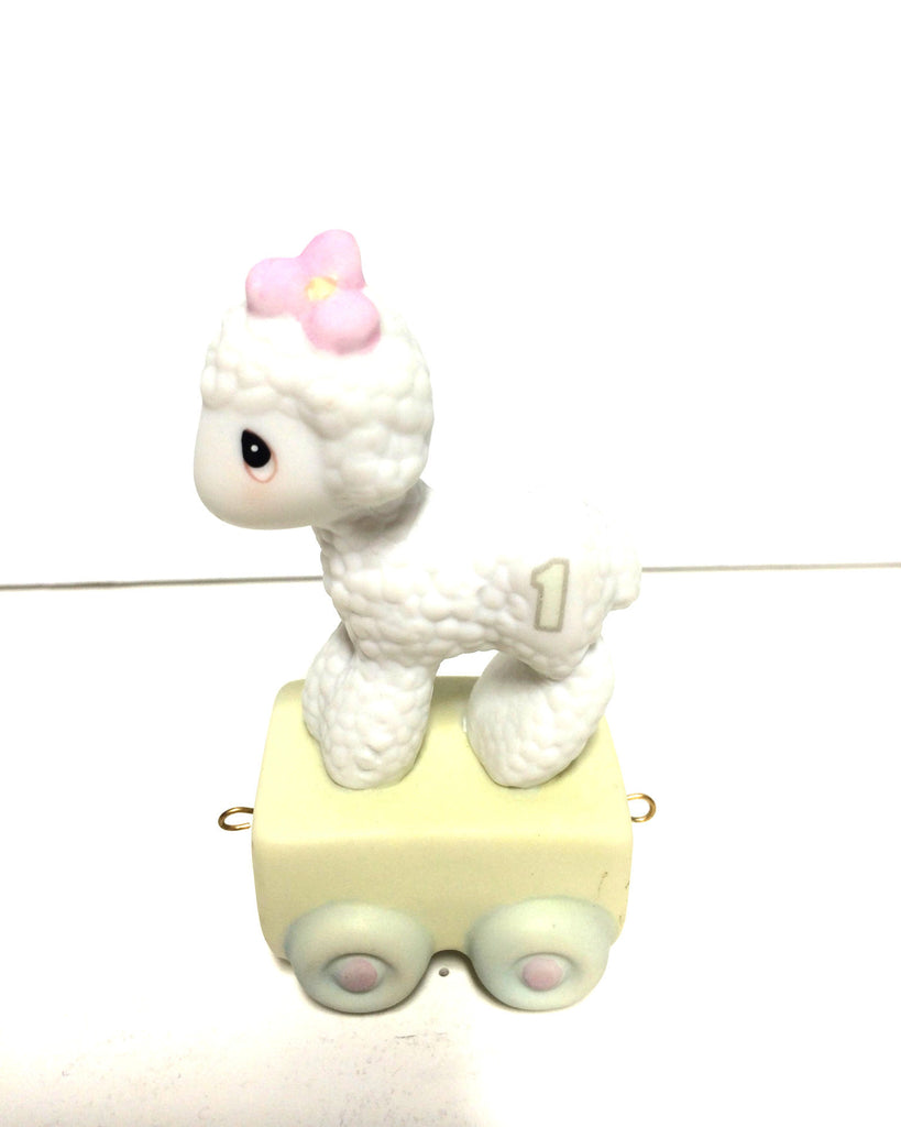 White Lamb w/ pink flower on head and number 1 on side. On yellow train car with wheels.