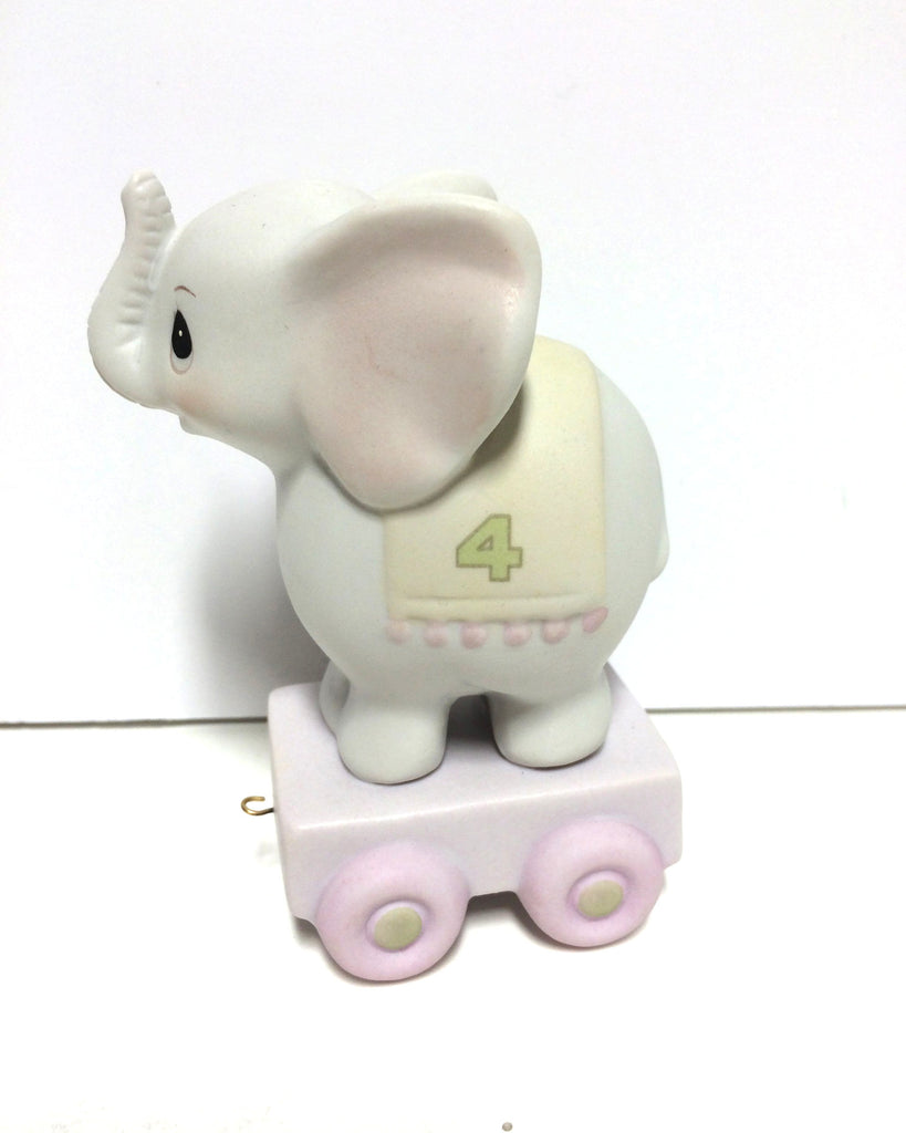 Baby elephant with 4 on green blanket. Sitting on train car