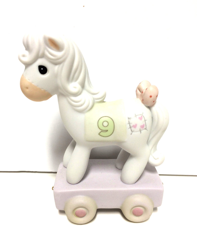 Beautiful white pony with bow on tail. Has 9 on side with a patch that has pink hearts on it. Standing on train car.