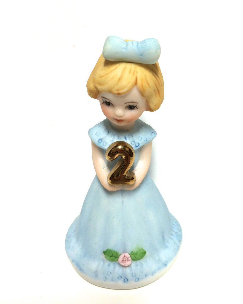 Blonde haired little girl dressed in blue holding the number 2.