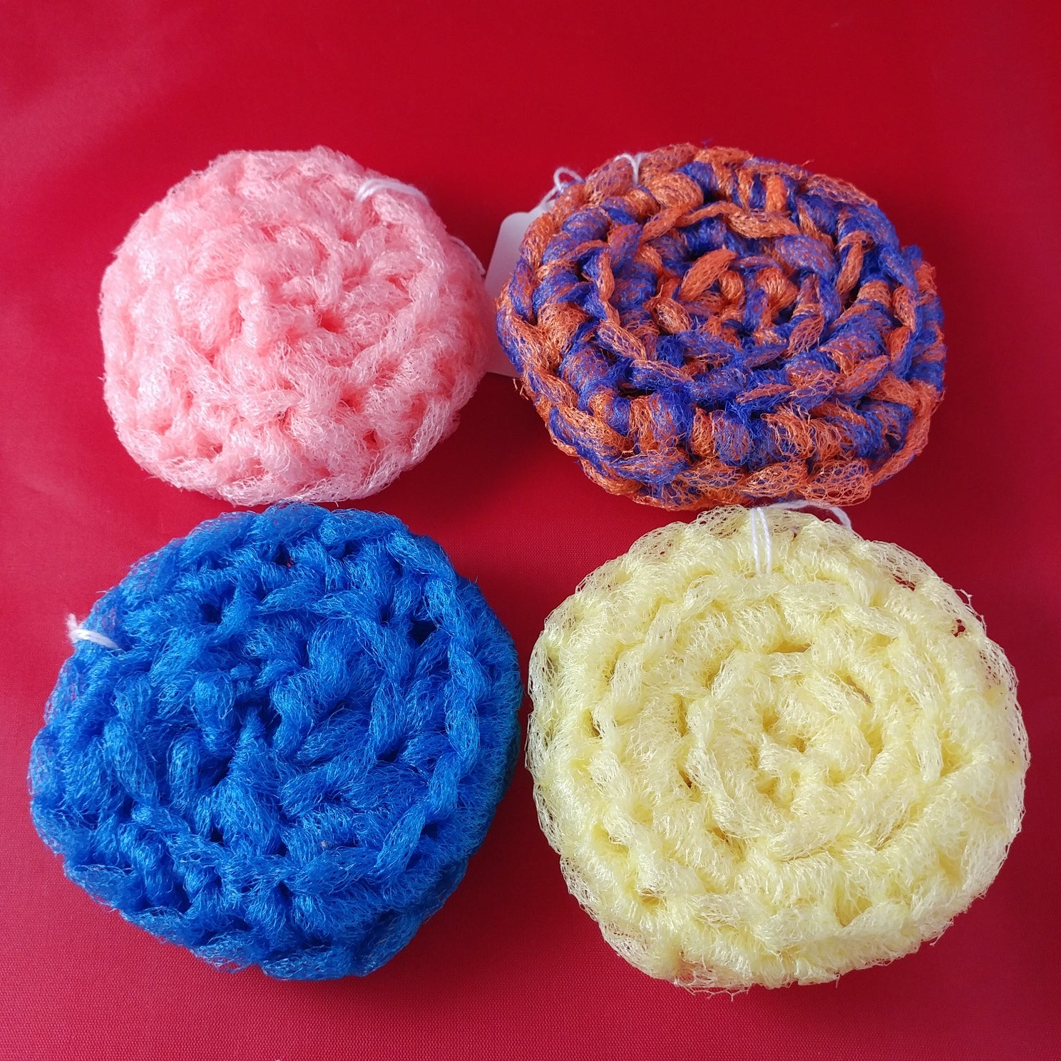 closeup photo of four crocheted scrubbies